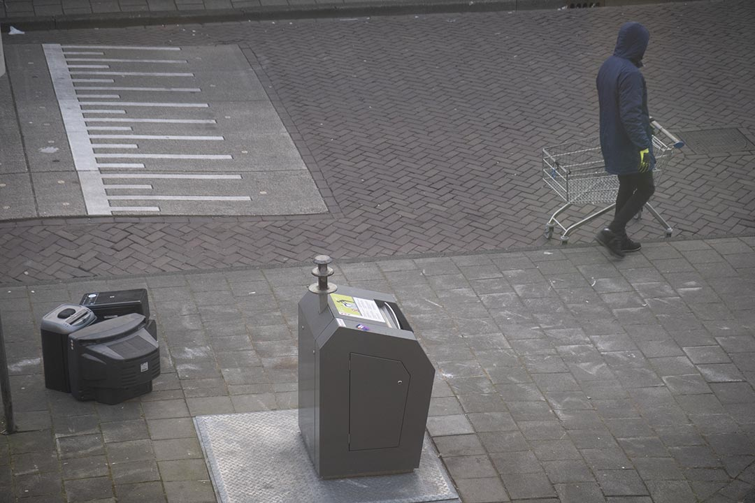 Bin with monitors and a person with a shopping trolley