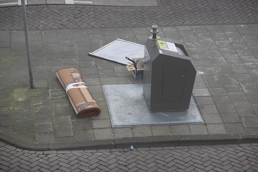Bin with rolled-up rug