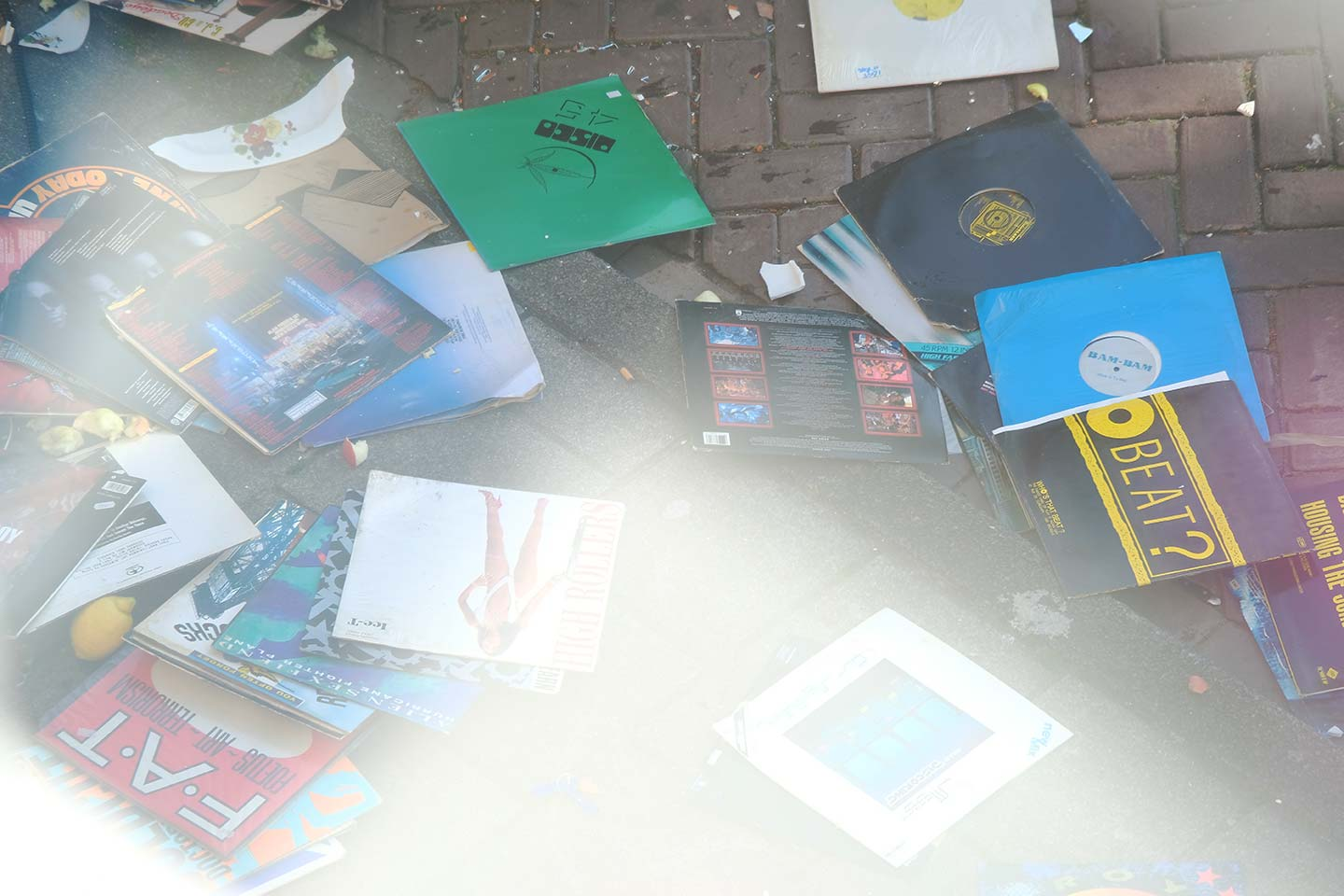 Records thrown from a window now on a pavement